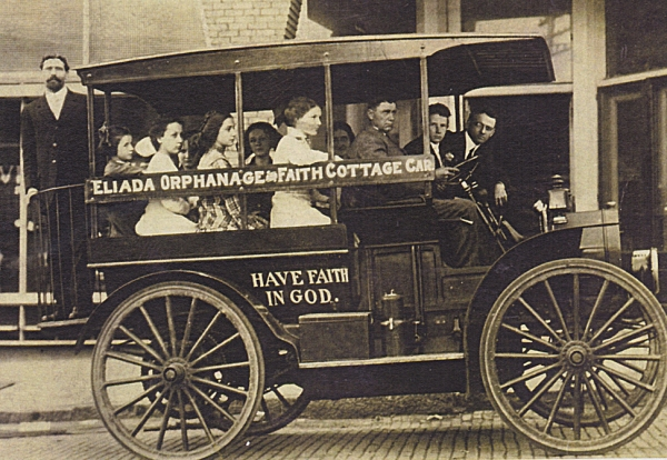 """The Gospel Wagon"" Rev. Compton, standing in back, heads into Asheville (Photo ca. 1911)."