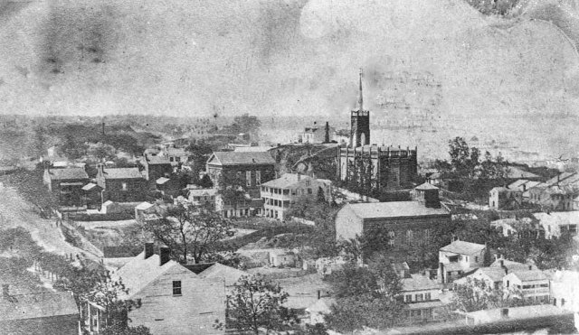 View of Vicksburg taken from the top of the courthouse looking to the southwest. In the distance is the spire of St. Paul's Catholic Church.