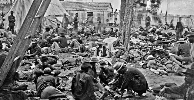 Union Field Hospital in Savage Station, VA with soldiers receiving care as they lay on the ground