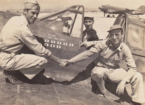 Maj Roland M Wilcox, on May 15, 1943, taken in Kunming China, serving with the 23rd Fighter Group, 75th Fighter Squadron of the Flying Tigers. That morning he had shot down 3 confirmed and 2 probable enemy aircraft in his P-40E. Pictured with Lt Col Bruce K Holloway, his daschund Joe, who had one zeke and one bomber that day, and Lt Charles Crysler who also had three confirmed and one probable victories that day.